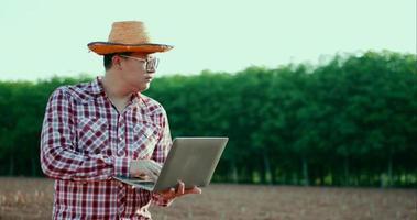 jovem agricultor verificando e coletando dados no laptop video