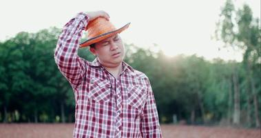 Young farmer take off hat and wipe sweat with tired video