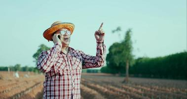 Happy young farmer use smartphone talking with proudly video