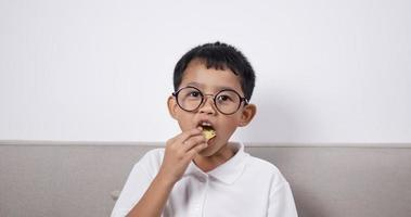 un garçon asiatique porte des lunettes assis sur un canapé et mange des chips. video