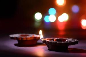 Clay diya lamps lit during Diwali Celebration. Greetings Card Design Indian Hindu Light Festival called Diwali photo