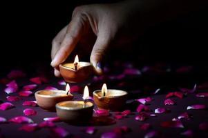 Hand holding and arranging lantern Diya during Diwali Festival of Lights photo