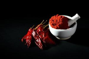 Red Chili Pepper powder in pestle with mortar and Red Chili Peppers on black background photo