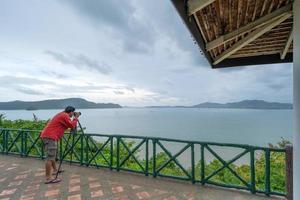 Fotógrafo profesional masculino en el mirador turístico toma una fotografía foto