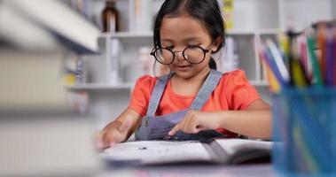 menina asiática de óculos praticando leitura na mesa na sala de aula. video