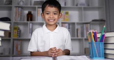 garçon assis sur le bureau et agitant les mains faisant des gestes bonjour ou au revoir. video