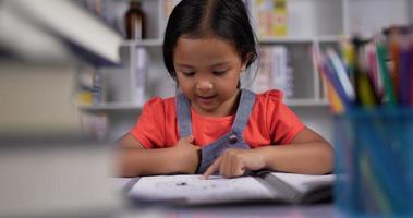 menina asiática praticando leitura na mesa na sala de aula. video