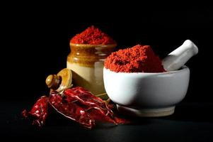 Red Chili Pepper powder in pestle with mortar and clay pot with Red Chili Peppers on black background photo