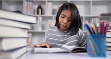 retrato de menina asiática de cabelo curto lendo na mesa na sala de aula. video