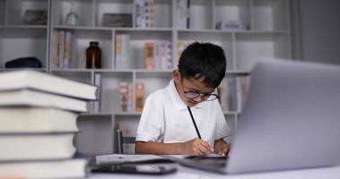 enfant garçon pensant et faisant ses devoirs à la maison. video
