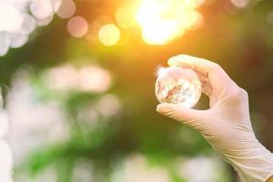 Globe glass on hand with sunrise photo