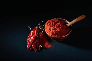 chilly powder in wooden bowl with red chilly, dried chillies on black background photo