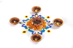 Clay diya lamp lit during diwali festival. Clay Diya on Rangoli. Happy Diwali Greetings Card Design, Indian Hindu Festival of Lights called Diwali. photo