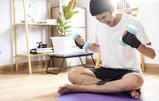 Hombre caucásico asiático sostiene pesas en casa foto