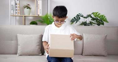 Boy wearing glasses opening gift box video