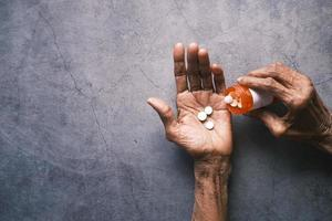 senior hand holding with pills on black background with copy space photo
