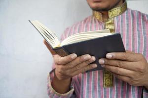 Mano de hombre musulmán leyendo el libro sagrado Corán con espacio de copia foto