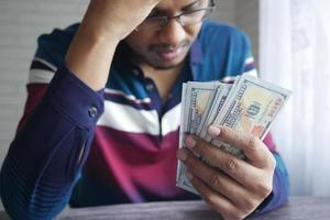 upset man hand holding 100 us dollar cash photo