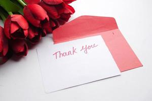 thank you message, envelope and red tulip flower on white background photo