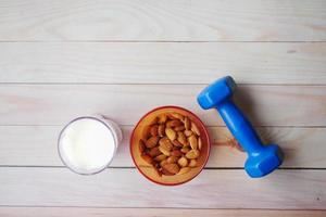 almond nut in a bowl, milk and dumbbell on table photo
