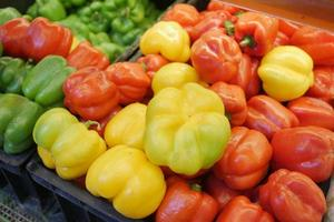 Yellow orange and red capsicum on display for sale photo
