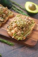 tuna fish and avocado on slice of a brown bread on table photo