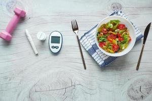 diabetic measurement tools and healthy food on table photo