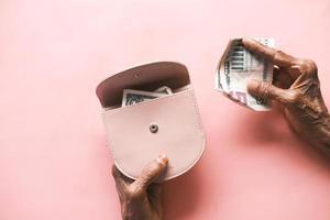 senior women hand saving cash in wallet photo