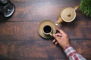 hand holding cup of green tea with copy space photo