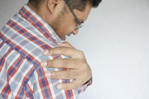 man suffering pain in hand looking down photo