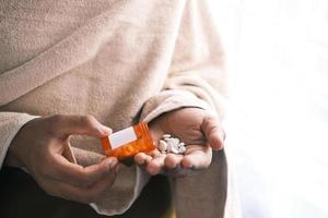 La mano del hombre con la medicina derramada fuera del contenedor de pastillas foto