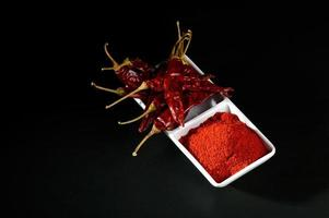 chilly powder with red chilly in white plate, dried chillies on black background photo