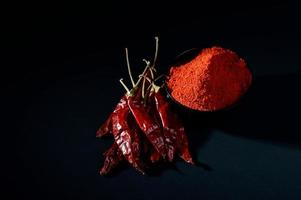 chilly powder in black bowl with red chilly, dried chillies on black background photo