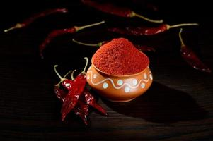 chilly powder in clay pot with red chilly, dried chillies on wooden background photo
