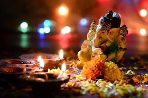 Clay diya lamps lit with Lord Ganesha during Diwali Celebration. Greetings Card Design Indian Hindu Light Festival called Diwali photo