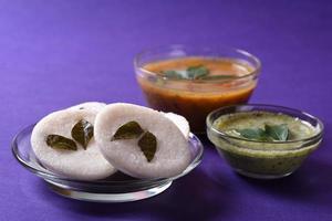 idli con sambar y chutney de coco sobre fondo violeta, plato indio, comida favorita del sur de la India, rava idli o sémola sin hacer nada o rava sin hacer nada, servido con sambar y salsa picante verde. foto