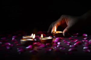 Hand holding and arranging lantern, Diya during Diwali Festival of Lights photo