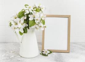 flor de manzana de primavera en un jarrón con un marco de fotos vacío