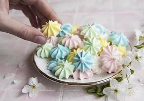 Small colorful meringues in the ceramic  plate photo