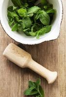 hojas de menta verde fresca en mortero foto