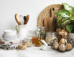 utensilios de cocina, herramientas y vajilla en la pared de azulejos blancos de fondo. foto