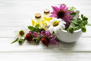 Medical flowers and plant in mortar and essential oils on a white wooden table photo