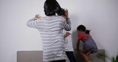 crianças asiáticas engraçadas dançando no sofá na sala de estar em casa. video