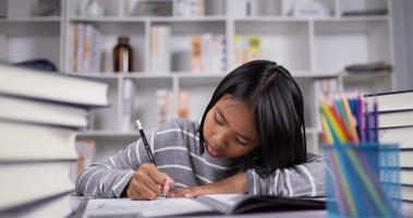 garota asiática de cabelo curto fazendo lição de casa na mesa na sala de aula. video