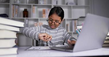 Happy asian teen girl wearing glasses typing on laptop and doing homework at home. video