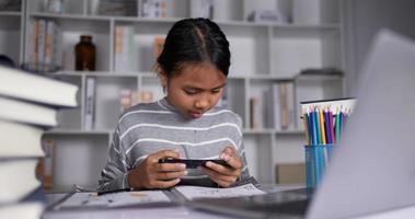 chica tailandesa jugando en el teléfono móvil y perdida mientras estudiaba en línea en casa. video