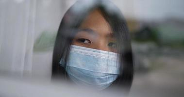 Teen girl wearing a surgical mask is looking out of the window. video