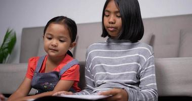 Handheld shot of The older sister teach the younger sister to read book video