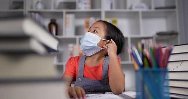 kleines Mädchen in medizinischer Maske, das zur Decke schaut und nachdenkt. video