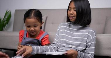 Handheld shot of Asian older sister teach younger sister to read book video